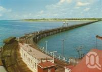 """<span class=""""caption-caption"""">Wharf and pier at Urangan</span>, c1970. <br />Postcard by <span class=""""caption-publisher"""">Murray Views Pty Ltd</span>, collection of <span class=""""caption-contributor"""">Centre for the Government of Queensland</span>."""