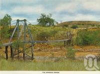 "<span class=""caption-caption"">The swinging bridge, Mount Morgan</span>, c1966. <br />Postcard folder by <span class=""caption-publisher"">Sydney G Hughes Pty Ltd</span>, collection of <span class=""caption-contributor"">Centre for the Government of Queensland</span>."
