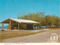 "<span class=""caption-caption"">Log cabin shelter, Woodgate Beach</span>, c1964. <br />Postcard folder by <span class=""caption-publisher"">Murray Views Pty Ltd</span>, collection of <span class=""caption-contributor"">Centre for the Government of Queensland</span>."