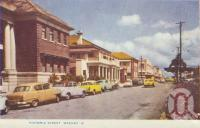 "<span class=""caption-caption"">Victoria Street, Mackay</span>, c1956. <br />Postcard folder by <span class=""caption-publisher"">Murray Views Pty Ltd</span>, collection of <span class=""caption-contributor"">Centre for the Government of Queensland</span>."