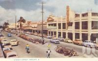 "<span class=""caption-caption"">Sydney Street, Mackay</span>, c1956. <br />Postcard folder by <span class=""caption-publisher"">Murray Views Pty Ltd</span>, collection of <span class=""caption-contributor"">Centre for the Government of Queensland</span>."