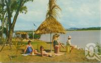 "<span class=""caption-caption"">At Eimeo Beach, near Mackay</span>, c1962. <br />Postcard by <span class=""caption-publisher"">Murray Views Pty Ltd</span>, collection of <span class=""caption-contributor"">Centre for the Government of Queensland</span>."